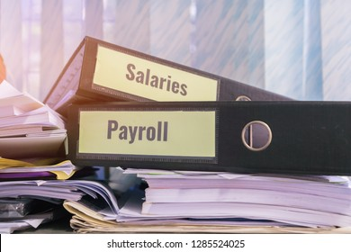 Payroll and salaries folders stack with label on black binder on paperwork documents summary report, HR-human resources business and bookkeeping accountancy concept in busy offices