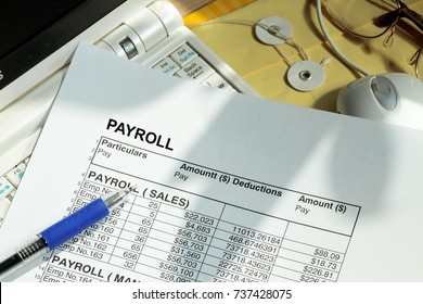 Payroll spreadsheet with computer monitor and mouse