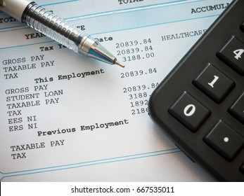 A payslip, pen and calculator