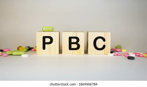 PBC Primary biliary cholangitis - word from wooden blocks with letters on white background surrounded with colorful pills.Medical concept.