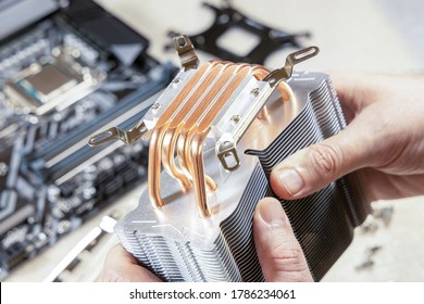 PC assembly. Technician's hands hold new CPU heatsink. Close-up