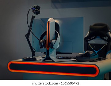 PC, keyboard and headphones with neon backlight. Gaming equipment