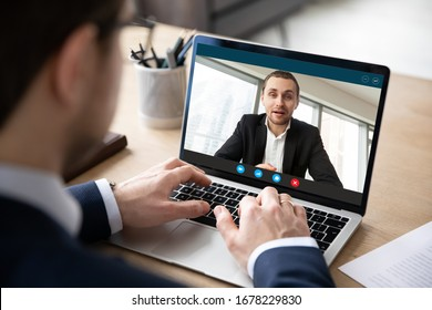 Pc screen view over businessman shoulder, due to corona virus all communications, business negotiations, perform distantly via videoconference, to exclude risk of infection outbreak and spread concept