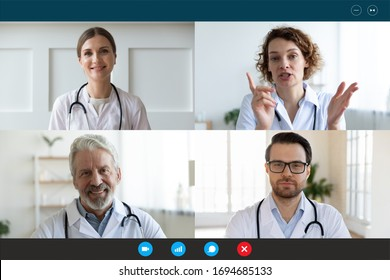 Pc screen webcam view, head shot portrait four diverse medical workers in white coats take part in distant talk, engaged in group video call. Videoconferencing, concilium remote communication concept