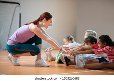PE teacher smiling. PE teacher wearing leggings smiling while helping dark-skinned girl stretching