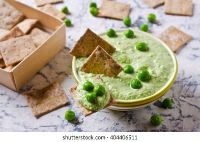 Pea green dip on a cracker. Selective focus.