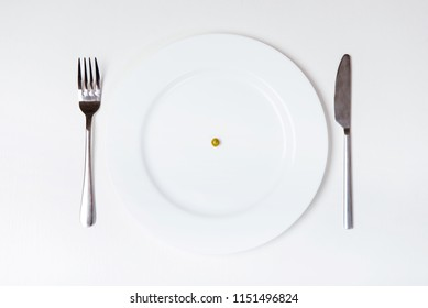 Pea on plate. Knife and fork. Isolated Background. Top Vew. Unhealthy Nutrition and Diets. Anorexia Concept. Equipment for Food. Teen Anorexic. Stainless Silver Set. Table on Studio.