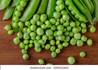 Pea pods on wooden table. Top view