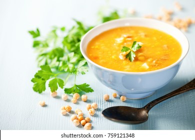 Pea soup with pieces of bacon and parsley in a bowl on a blue background. Selective focus