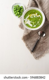 Pea soup puree in an old white bowl with parsley decoration. White wooden background.