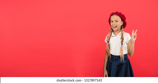 Peace to all. Little kid wearing stylish french beret. Cute girl having trendy hairstyle. Small child with long hair plaits. Fashion girl with tied hair into braids. French style girl, copy space.