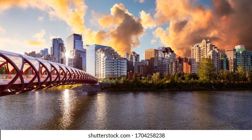Peace Bridge across Bow River with Modern City Buildings in Background during a vibrant summer sunrise. Cloudy Sky Composite. Taken in Calgary, Alberta, Canada.