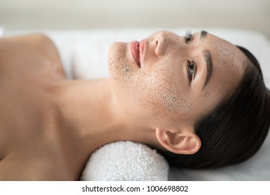 Peace and comfort. Close up of serene asian girl lying with scrub mask on her face at spa