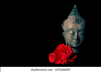 Peace and love. Traditional meditating Buddha head with red roses isolated on black background copyspace. Beautiful peaceful image. Calm Buddhist mindfulness. Zen Buddhism. Spiritual enlightenment.