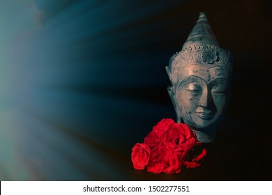 Peace and love. Traditional meditating Buddha head with red roses isolated on black background with copyspace. Beautiful peaceful image. Calm Buddhist mindfulness. Zen Buddhism. Spiritual love.