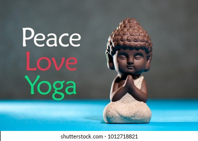 Peace love yoga - concept of freedom and happiness. figurine of babby buddha or little prayer practicing yoga or meditate