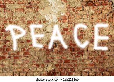 PEACE, spray paint on a damaged brick wall