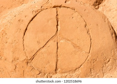 Peace symbol drawn in the sand on the beach