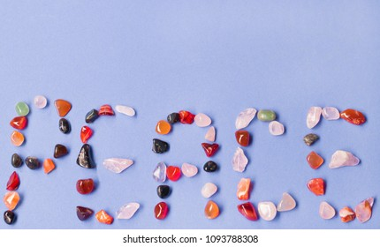 Peace - written with colorful stones on pastel blue background