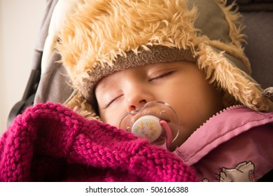 Peaceful 8 months old baby from Slovenia sleeping in baby carriage (stroller) - cosy in hat outdoor in cold winter weather