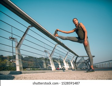 Peaceful athlete standing on the bridge with closed eyes and one foot on the banister