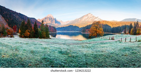 Peaceful autumn view on Obersee lake in Swiss Alps. Frosty grass and mountains reflections in clear water. Nafels village, Switzerland. Landscape photography