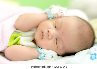 Peaceful baby lying on a bed while sleeping in a bed room