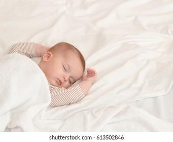 Peaceful baby lying on a bed while sleeping in a bright room. Newborn Sleep. Hands behind head. Happy motherhood concept