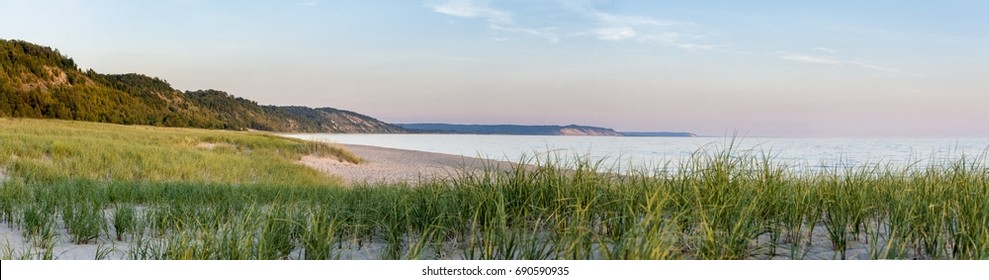 Peaceful beach dunegrass and sunset photo for calming relaxation summer getaway concept.  Wide panoramic photo in high-definition.