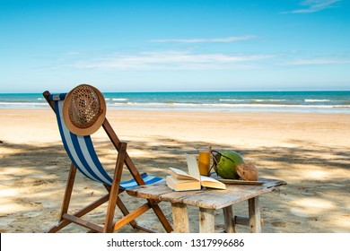 Peaceful beach scenery with a vintage deck chair wooden table, book and coconut s.
