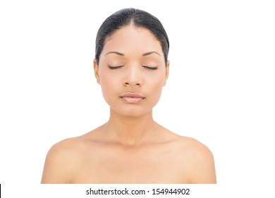 Peaceful black haired woman posing on white background