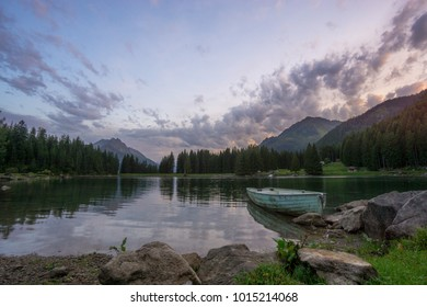 Peaceful blue hour atmosphere at a mountain lake in the Swiss Alps after an intense thunderstorm passed by. Inviting boat lies next to the shore of the lake and the reflections are amazing. Cloudy sky
