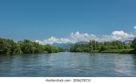 A peaceful blue river flows between the banks with lush green vegetation. In the distance, against the background of the azure sky and clouds, a mountain range is visible. Kamchatka
