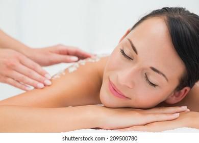 Peaceful brunette getting a salt scrub beauty treatment in the health spa