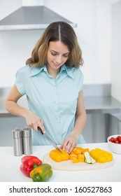 Peaceful brunette woman cutting vegetables standing in her kitchen at home
