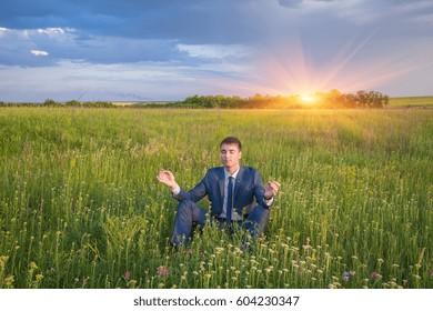 Peaceful businessman sitting in lotus pose relaxing against nature scene