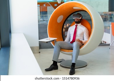 Peaceful businessman in VR headset enjoying virtual video. Man in office clothes and virtual reality goggles sitting in interactive chair and relaxing. Virtual content watching concept