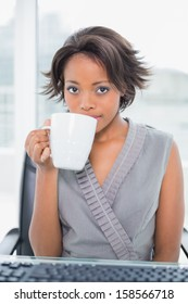 Peaceful businesswoman drinking coffee while having break in her office