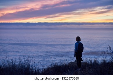 Peaceful California coast lifestyle photograph of woman standing in grass, watching the ocean and clouds and sunset