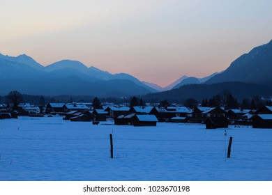 Peaceful and charming sunset in a village located in the snowy valley between peaks of Alps. Mountain silhouettes and colorful soft glowing sky. Garmisch Partenkirchen, Bavaria, Germany