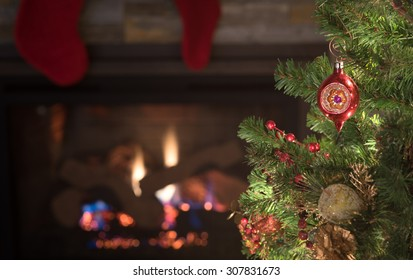 Peaceful Christmas Tree Scene with Vintage Red Ornament, stockings, lights, fireplace, dried cranberries with background room or space for copy, text, your words. Horizontal dark moody closeup.