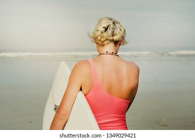 A peaceful close-up of a woman surfer's back as she walks out to a tranquil sea. She carries a surfboard and wears a pink swimming costume. Soft filters.