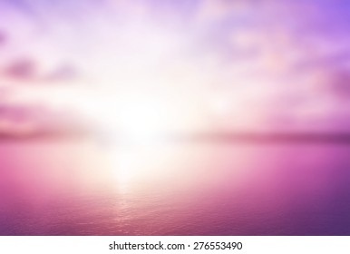 Peaceful concept: Abstract blur beautiful purple ocean with pink sky sunset background