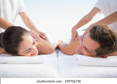 Peaceful couple enjoying couples massage poolside outside at the spa