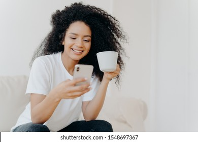 Peaceful curly woman scrolling social networks via modern mobile phone, watches funny videos, views photos in social networks, drinks coffee, poses on couch in living room, gets high paid job offer
