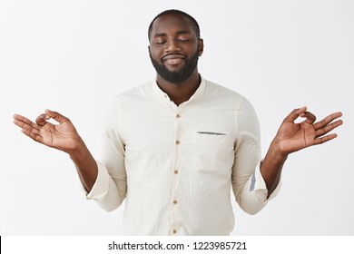 Peaceful and delighted African-american bearded male feeling nirvana smiling from pleasure as meditating with lotus pose and yoga orbs, close eyes releasing stress, feeling calm over gray wall