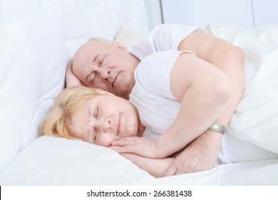 Peaceful dreams. Romantic elderly couple with head to head lying in bed asleep