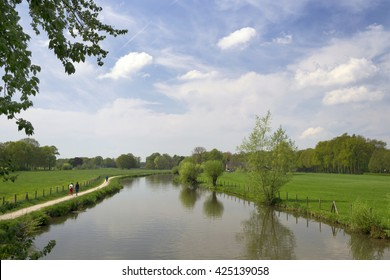 Peaceful Dutch landscape near the river Kromme Rijn, Rhijnauwen, Utrecht, the Netherlands  with water, trees, wanderers, meadows, walkway, blue sky and clouds. Ideal for recreation.