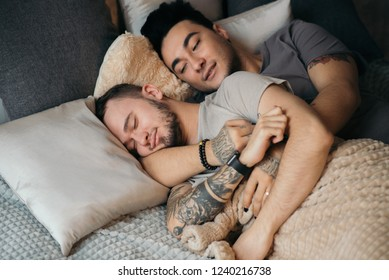 Peaceful european gay couple sleeping at home embracing and spending weekend together. Homosexual love concept