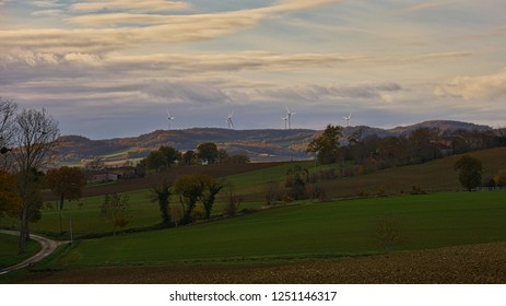 Peaceful farmland with wind turbines on the hill behind